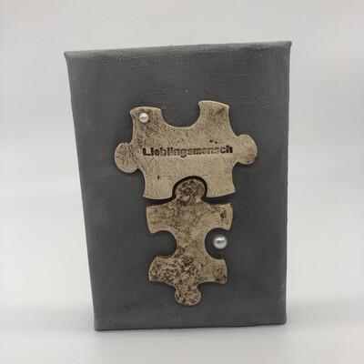Bild in Betonoptik mit Puzzleteilen