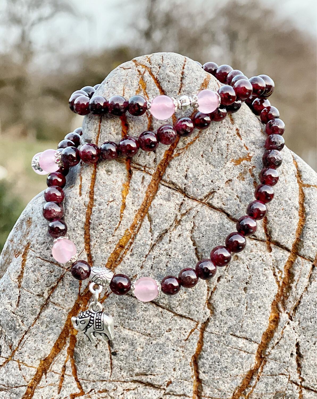 Mala grenat et quartz rose avec breloque éléphant sur élastique. Ce mala n'a que 94 perles au lieu de 108 chez les autres malas de cette boutique.