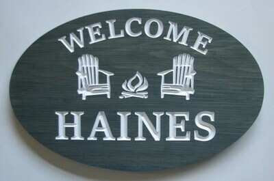 Stained Wood Oval Welcome Sign with Carved Chairs and Firepit