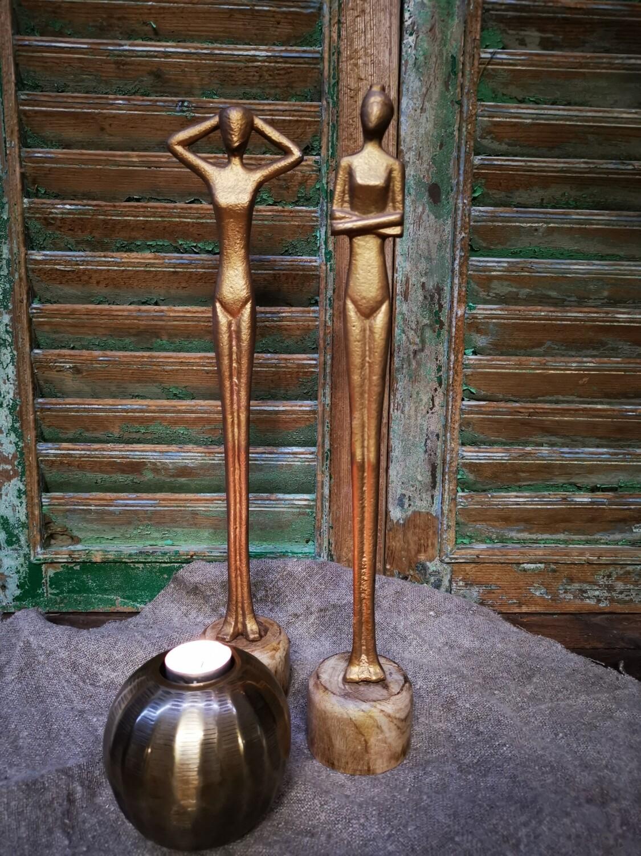 Metalen vrouwenbeeld op hout