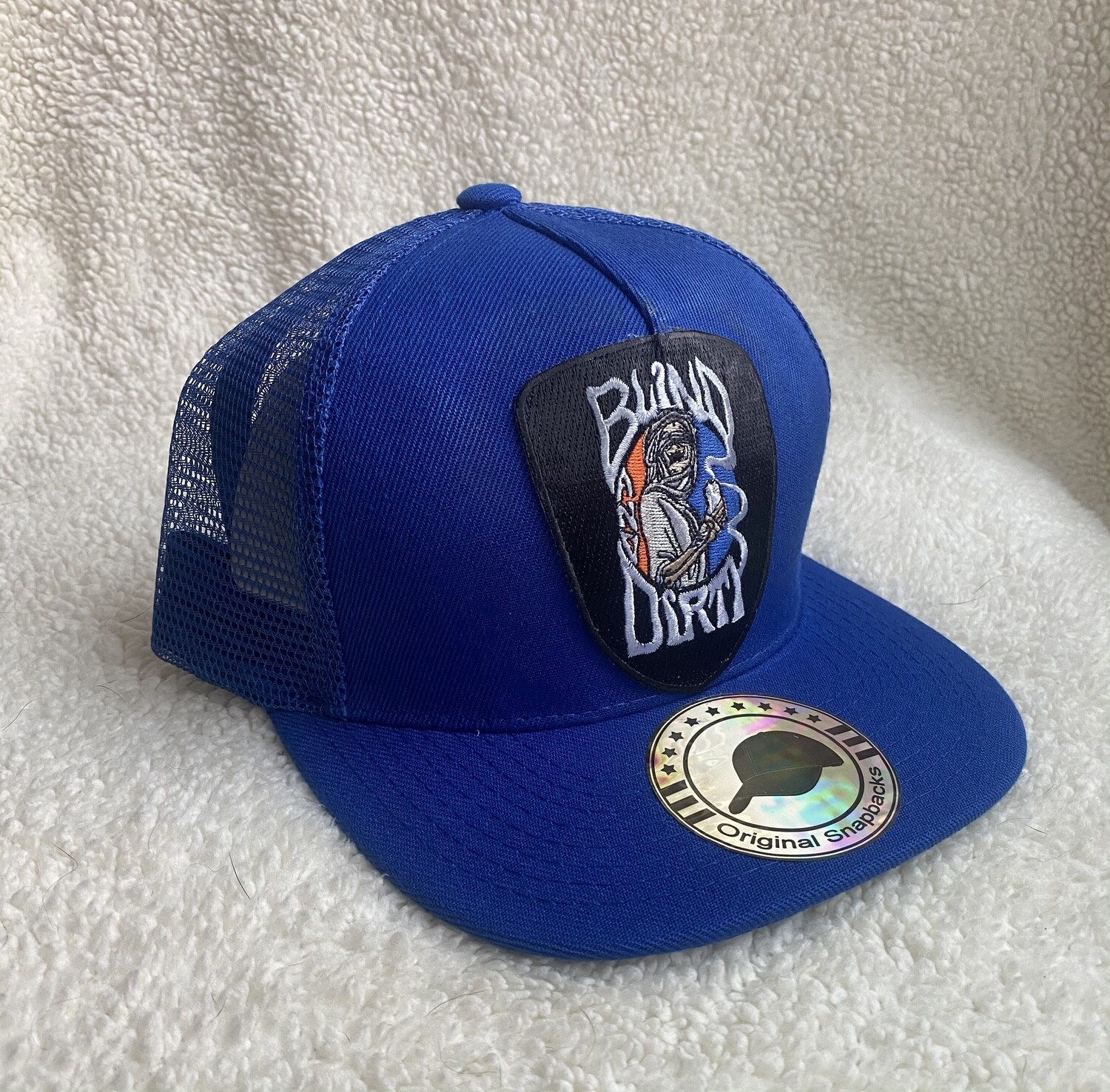 Trucker hat with custom embroidered patch, royal blue