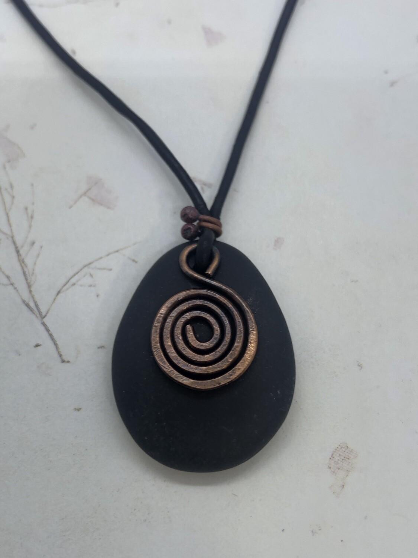 Beach stone pendant with copper spiral design