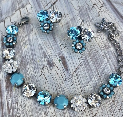 """The name of this bracelet is, """"A Touch Of Turquoise."""" This bracelet has opal and turquoise flowered elements with Swarovski stones. The setting is antique silver."""