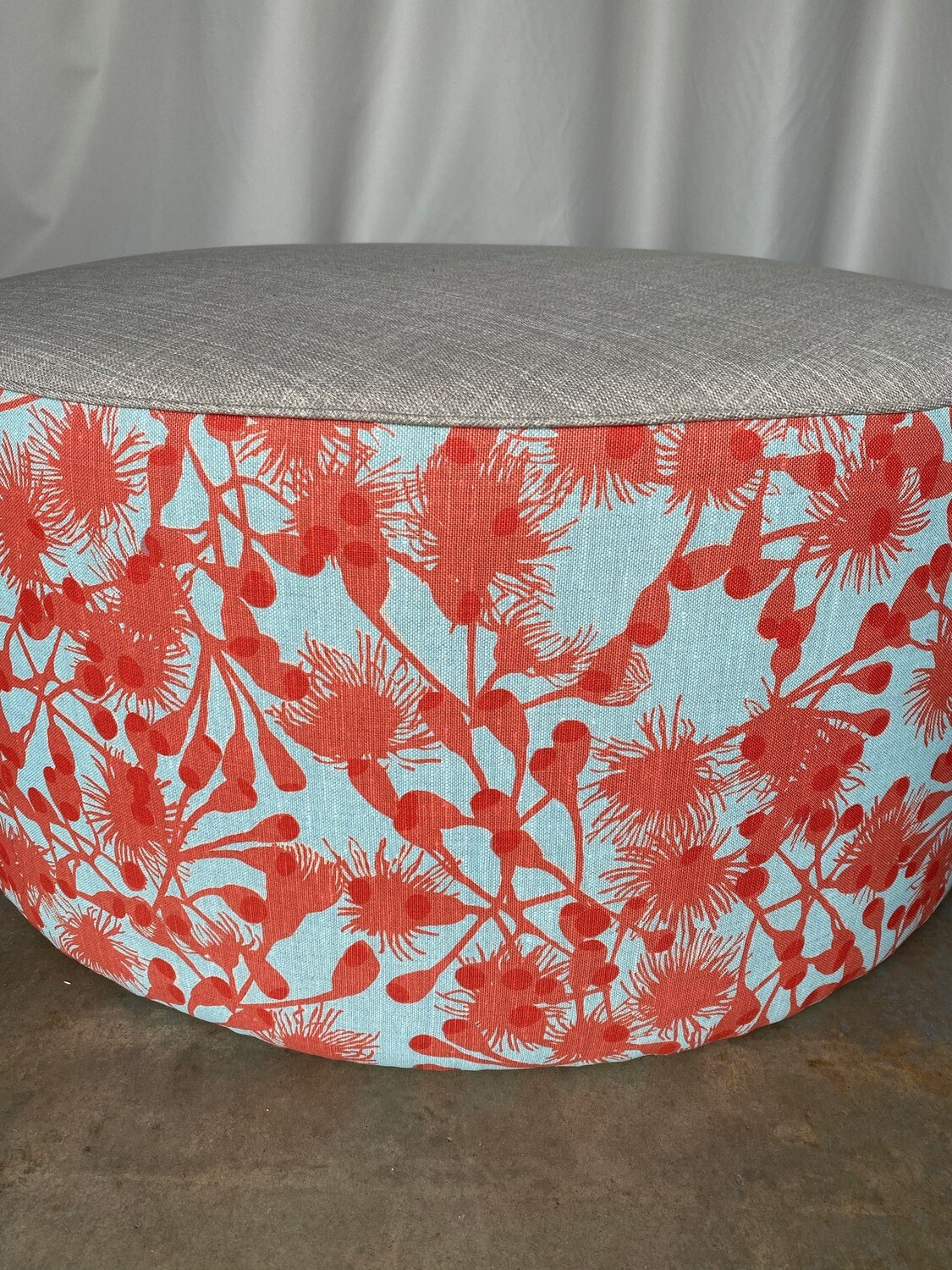 Large round ottoman with hand-screenprinted fabric and feather scatter cushion