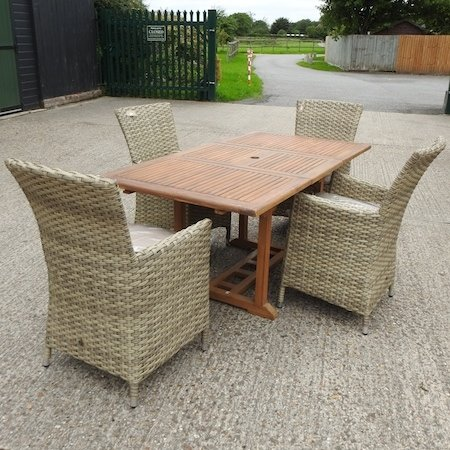 Lot 33,   A teak garden table, together with a set of four rattan garden chairs, with loose cushions 150/250