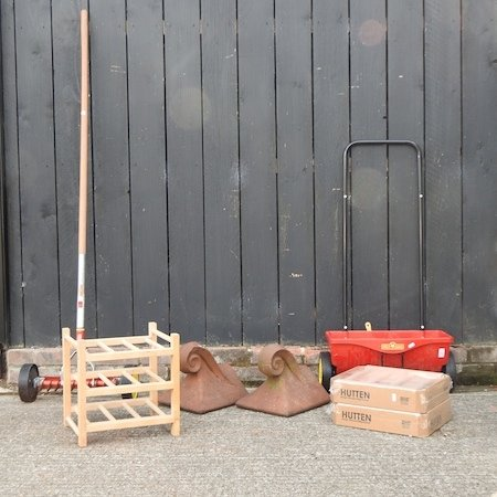 Lot 45,   A terracotta ridge tile, together with another, wine racks, 32cm, and garden tools 30/40