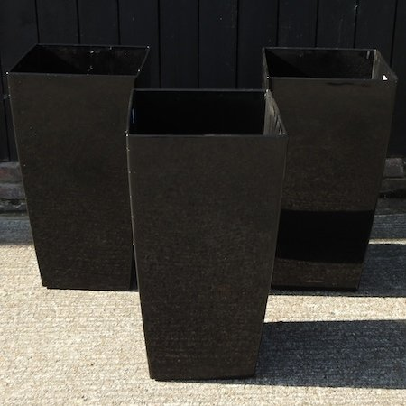 Lot 53,   A set of three black garden pots, 75cm high 20/40