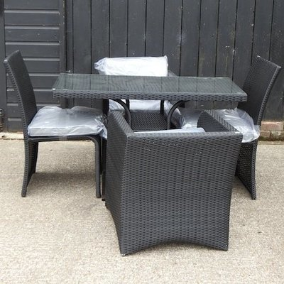 Lot 4,   A rattan garden set, comprising a table 120 x 60cm and set of four chairs, with grey cushions 150/200
