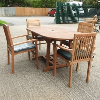 Lot 49,   A teak oval garden table, together with four teak chairs 150/200