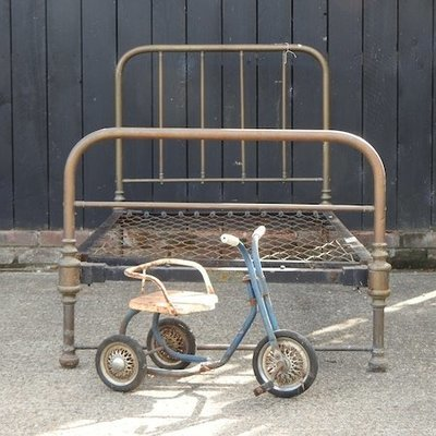 Lot 52,   A brass single bedstead, 185 x 91cm, together with a child's tricycle 30/50