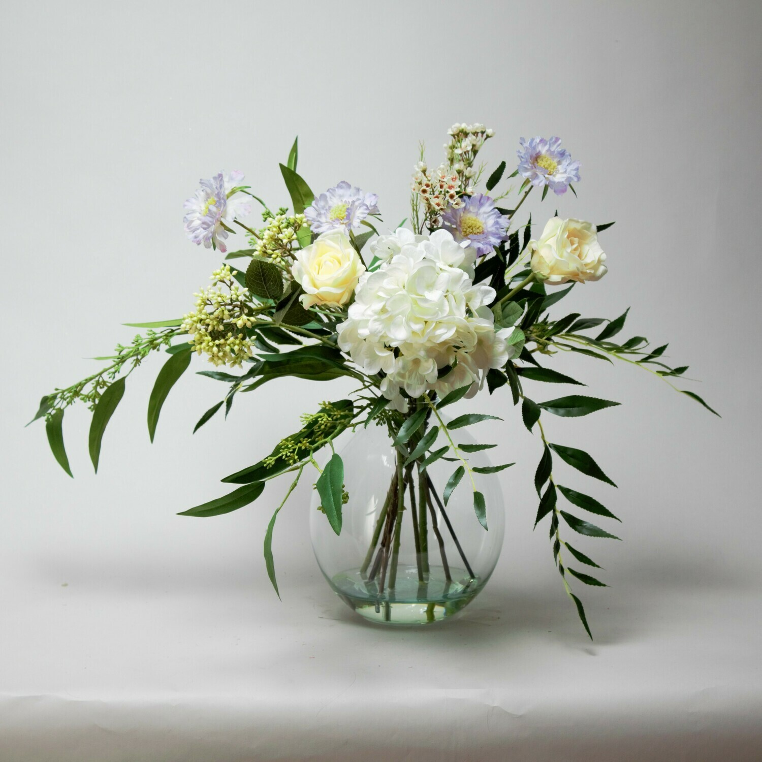 Hydrangea, Rose and Scabiosa Mix with Wild Foliage in an Oval Vase