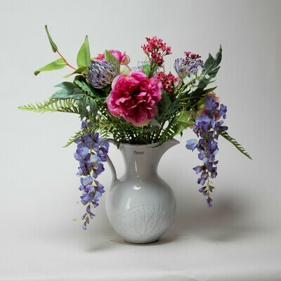 Peony, Wisteria and Protea mix with garden foliage in a lace jug