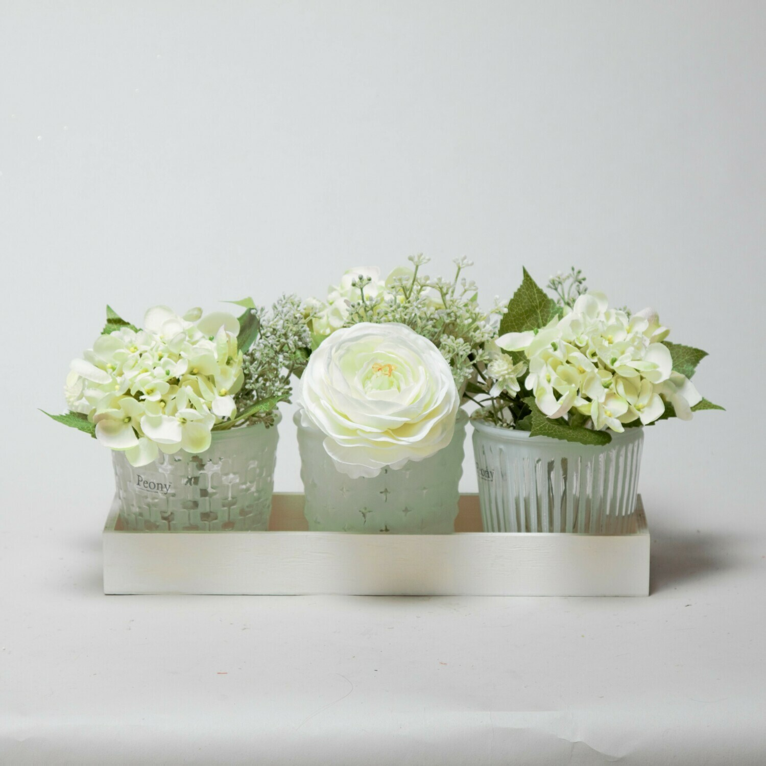 Set of three Hydrangea, Ranunculi and Eucalyptus seed in a wooden tray