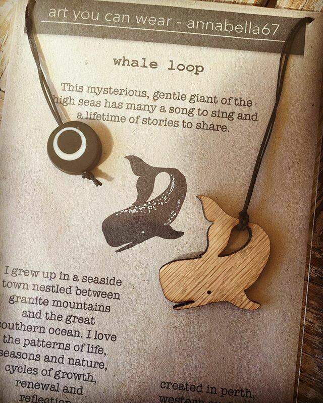 Whale Loop wood pendant on black waxed hemp