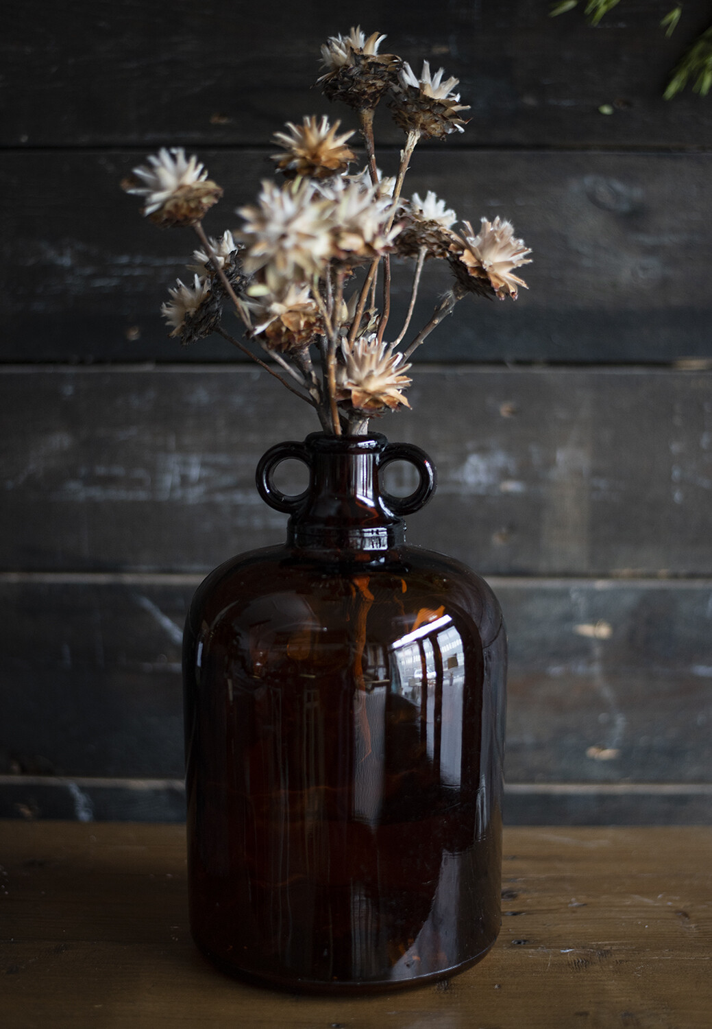Large brown glass vase with dried flowers