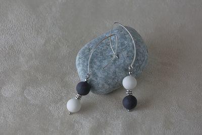 Длинные серьги, украшенные большими шариками из белого и черного фарфора. Long earrings decorated with large balls of white and black porcelain.