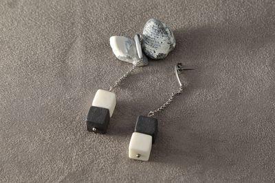 Ассиметричные серьги из черного и белого фарфора, кубики на длинной цепочке. Asymmetric earrings made of black and white porcelain, cubes on a long chain.