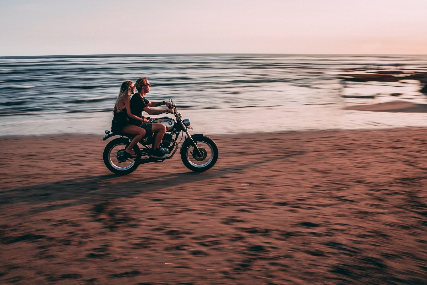 A couple riding a motorbike on the beach