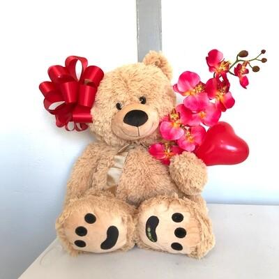 Giant plush teddy bear holding a balloon heart