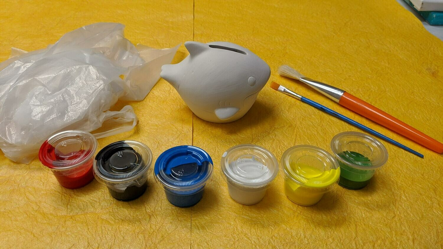 Various Plaster Figurines to paint for kids' Art Craft Activity or Birthday activities with brushes, paints, and apron.