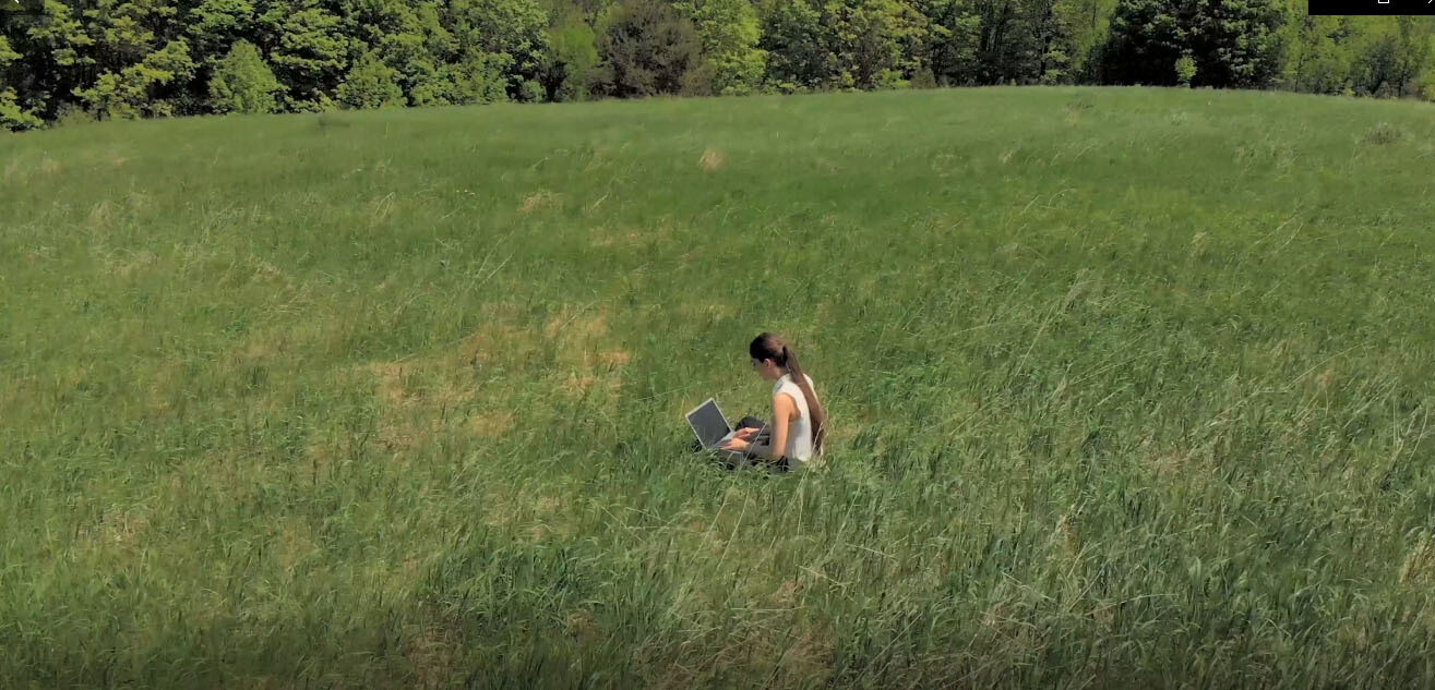 Drone circles woman working on laptop in field. 8 Bonus clips.