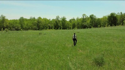 Young Woman walks straight away  in Grassy Field while carrying  an office book.  (2)