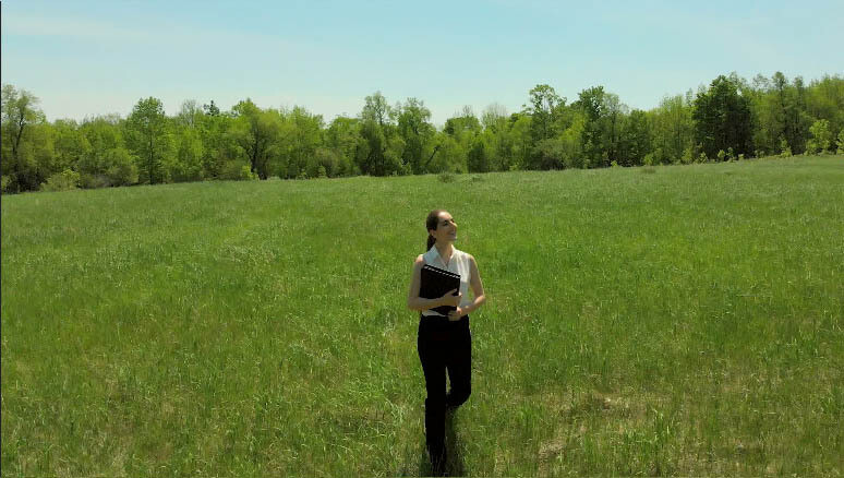 Young woman strides towards you holding an office book in a sunny field. (7)