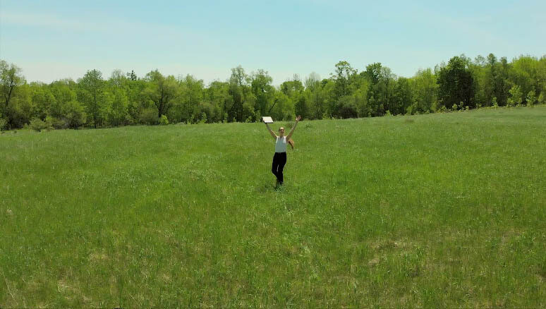 Young Woman Spins on Sunny Field holding office book twice, Hurray! (5)