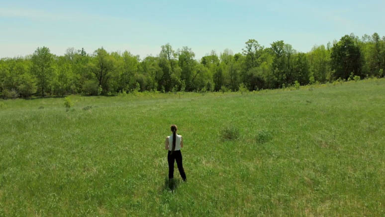 Young Woman walks away in Sunny Field holding office book. (6)