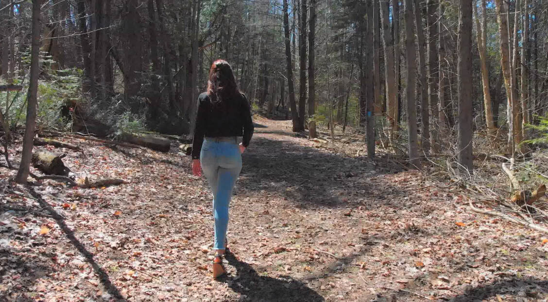 Woman Walking on Forest Path