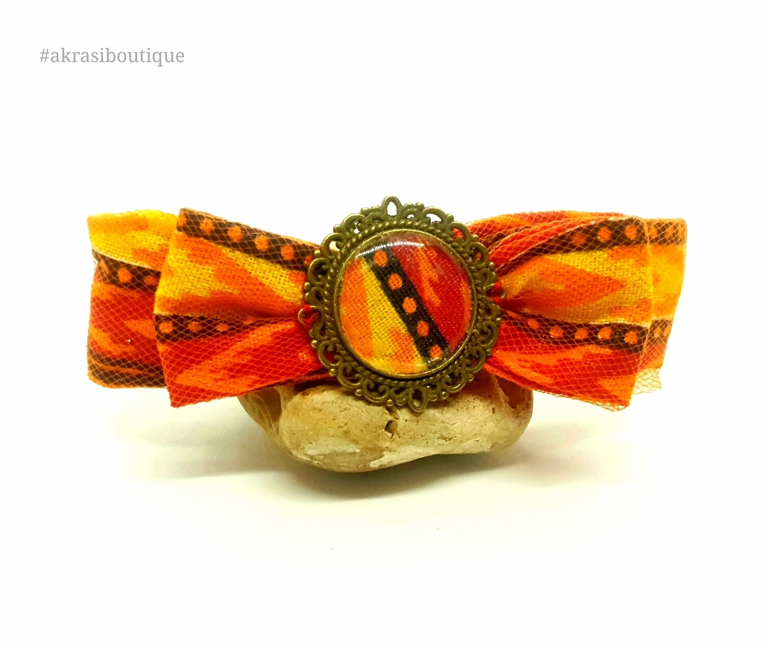 Dashiki bow barrette hair clip in orange netting with round bronze detail centre