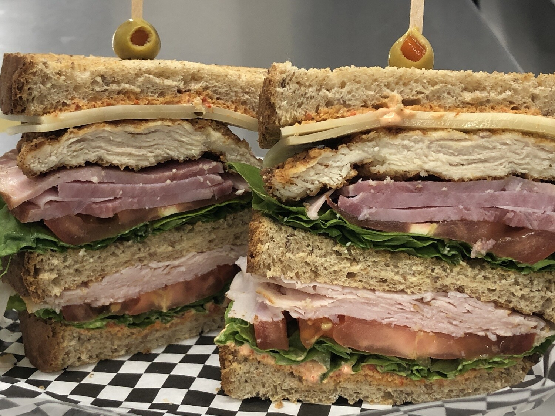 Airport Club-Bacon, Turkey, Ham, Avocado, lettuce, tomato, onion, roasted red pepper aioli on toasted wheatberry bread