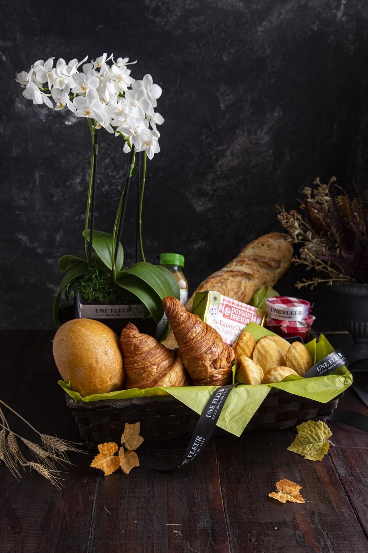 Cesta de café da manhã com sotaque francês acompanhado por orquidea em vaso