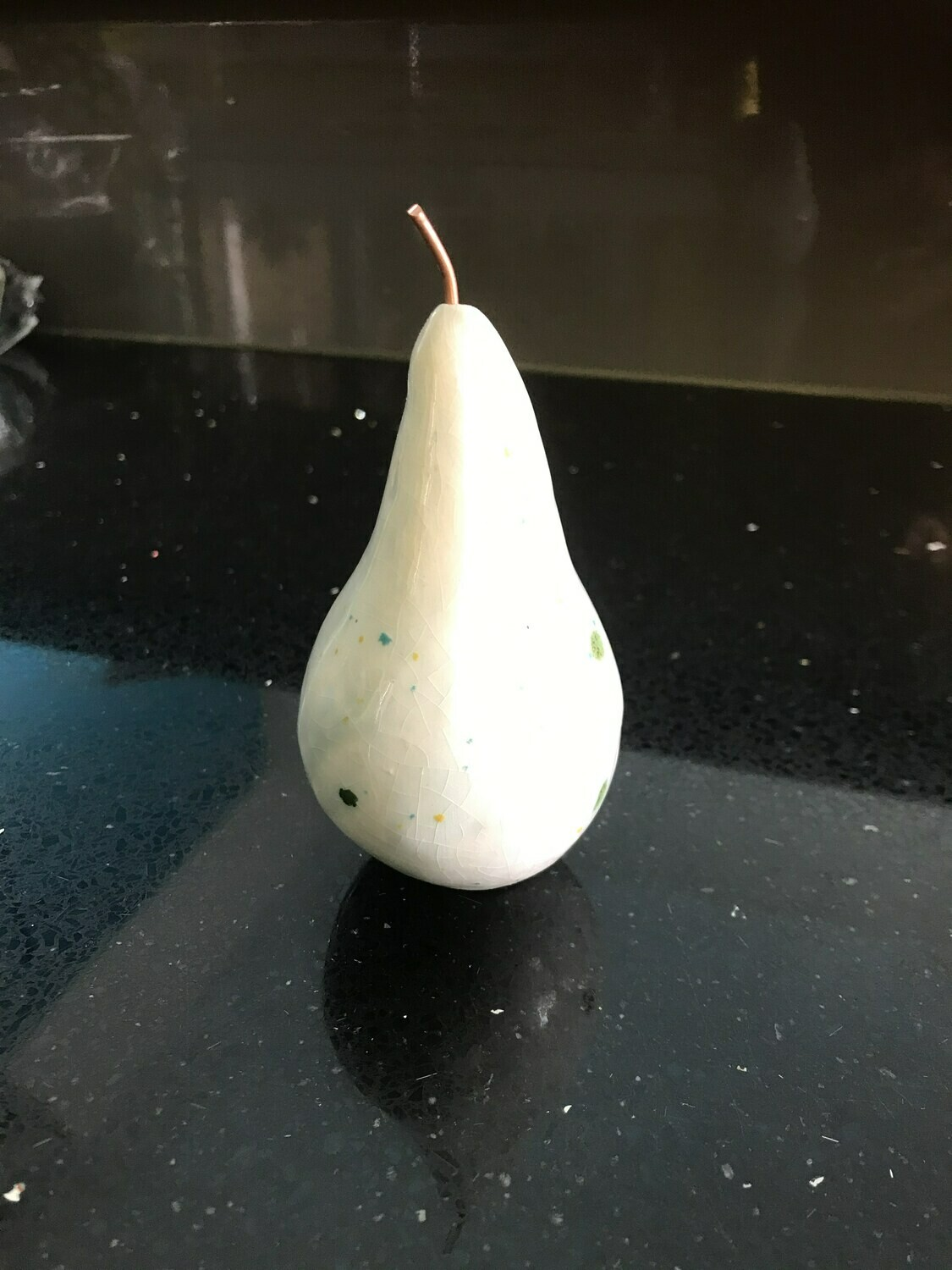 Ceramic pear with speckled glaze and copper stalk