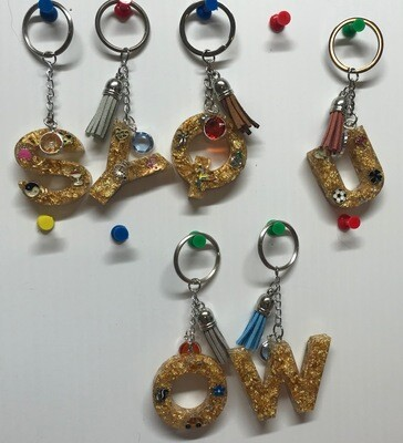 Small charms with gold flake letter or number keychain with  and small charms And tassel