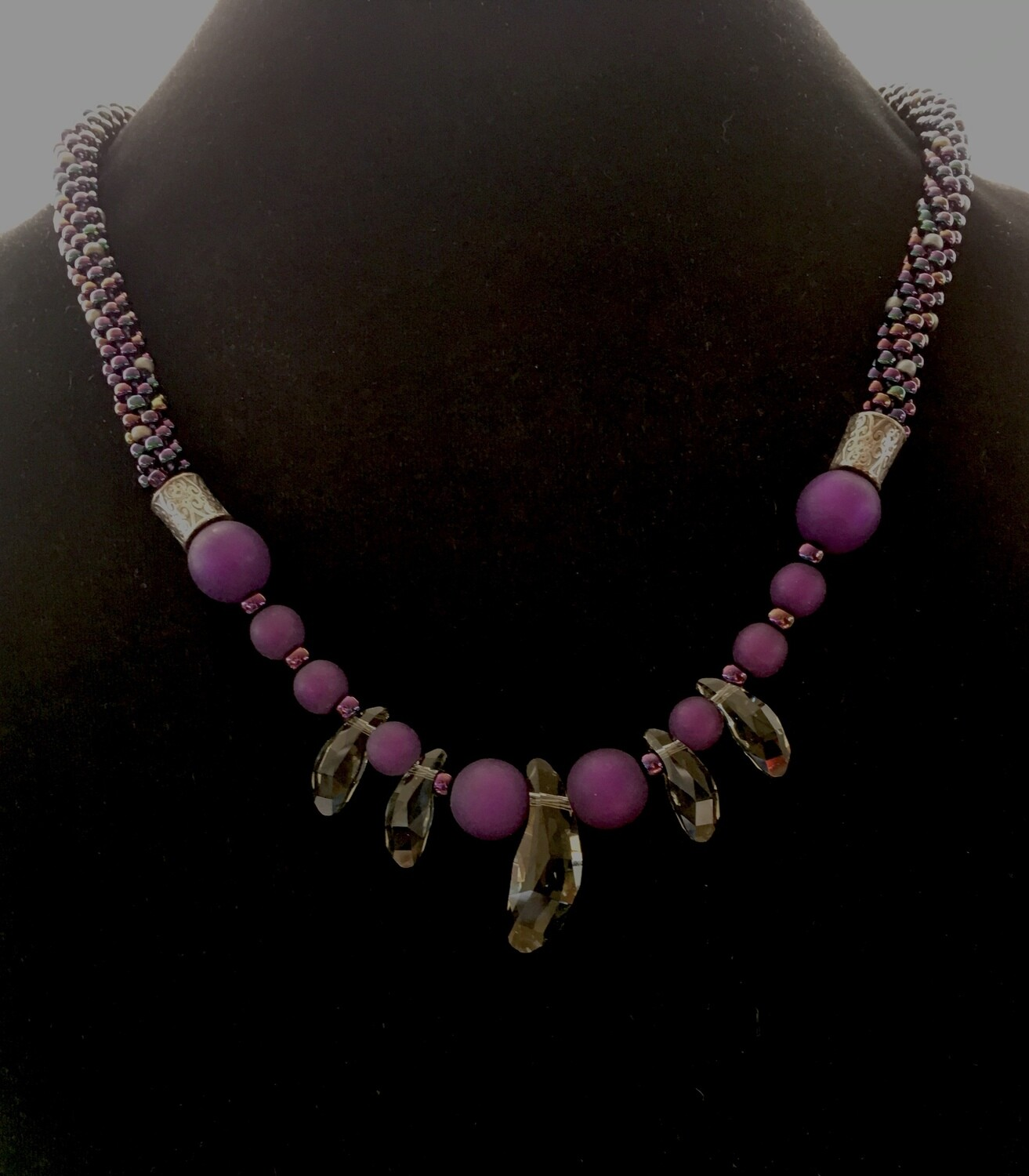 Purple Kumihumo necklace with glossy beads and dagger crystal pendant