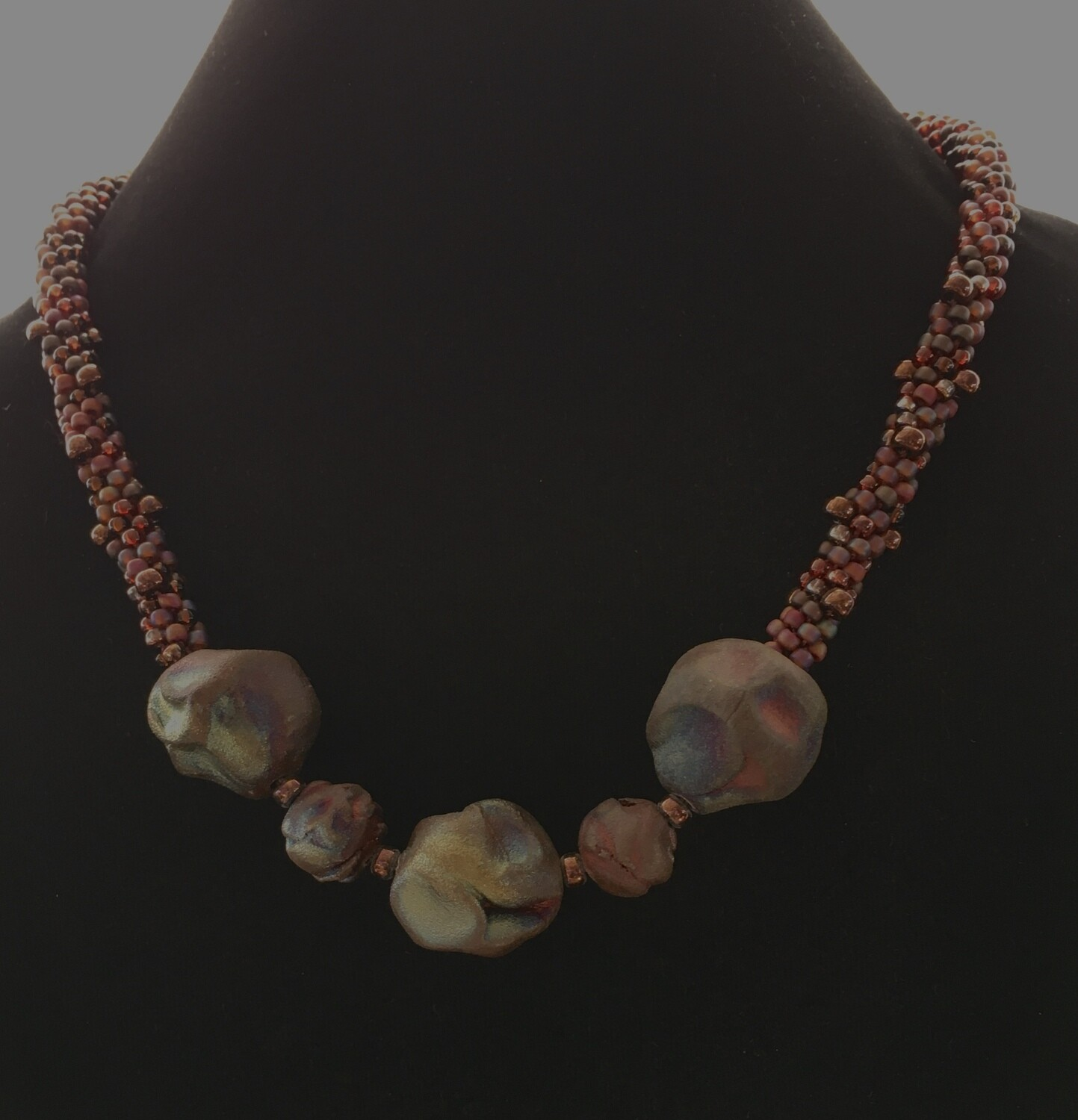 "Mauve coloured Kumihumo with ""pebble "" focal beads"