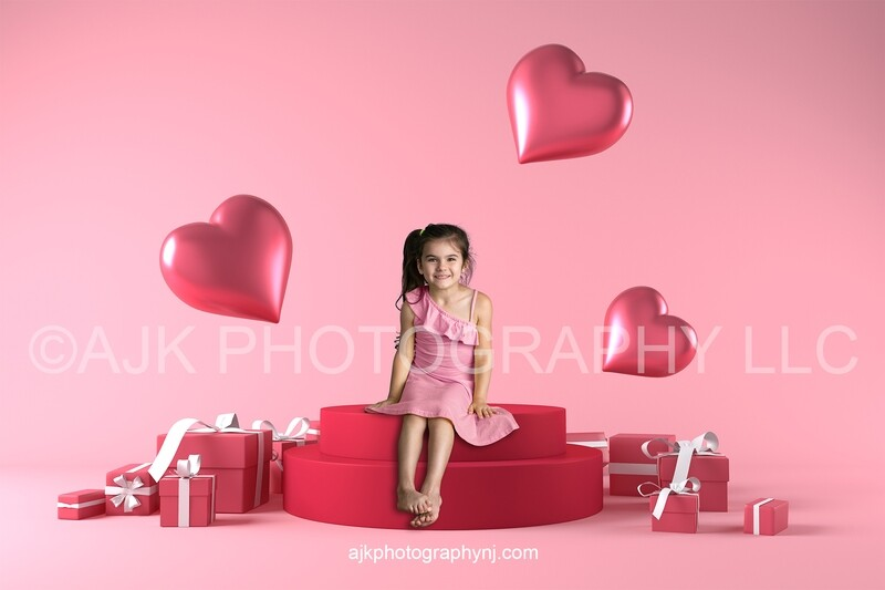 Valentine digital backdrop, child sitting on large red stage next to red Valentine gift boxes and pink hearts, digital background