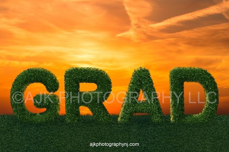Giant bush letters spelling GRAD in grassy field and golden sky, Graduation digital backdrop