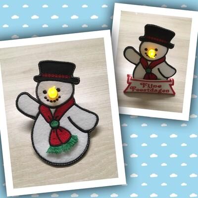 Sneeuwpop met plastic waxine lichtje als neus en fringe das