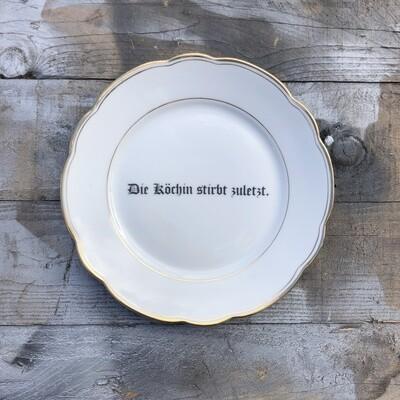 Porzellanteller >Die Köchin stirbt zuletzt.<