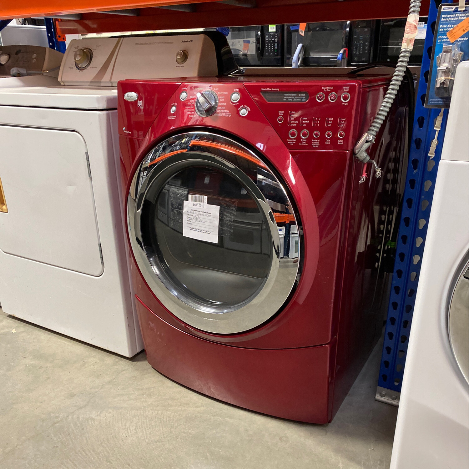 red whirlpool dryer and pedistal