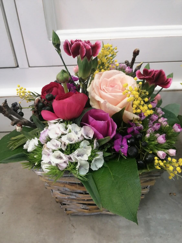 Arrangement de fleurs piquées dans  les tons pastels.