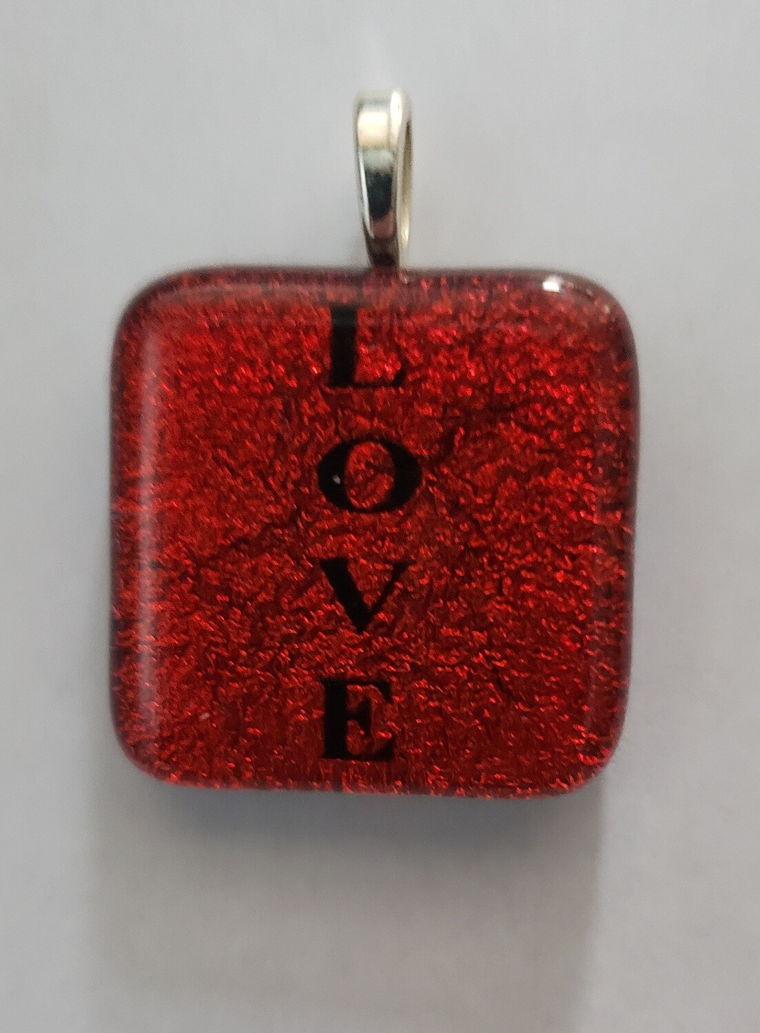 "Red dichroic glass pendant etched with ""Love"""