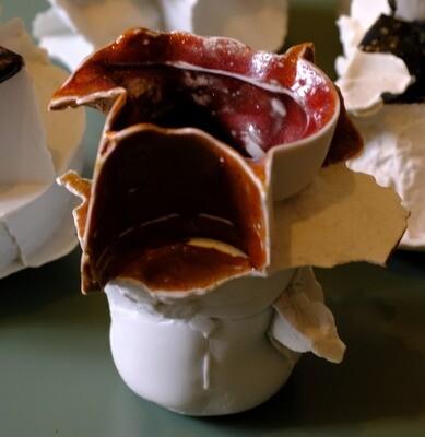 Vase en biscuit de porcelaine avec une large colerette découpée émaillé rouge et arborant des reflets marron.