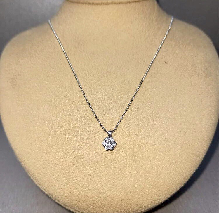 Cadena y colgante de oro blanco, con colgante tipo orla, con diamantes talla brillante con un peso de 0,12 ktes.