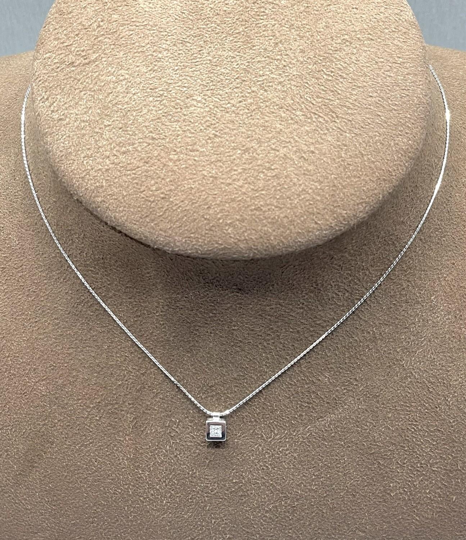 Cadena y chatón de oro blanco, con un diamante talla princesa con un peso 0,27 ktes.