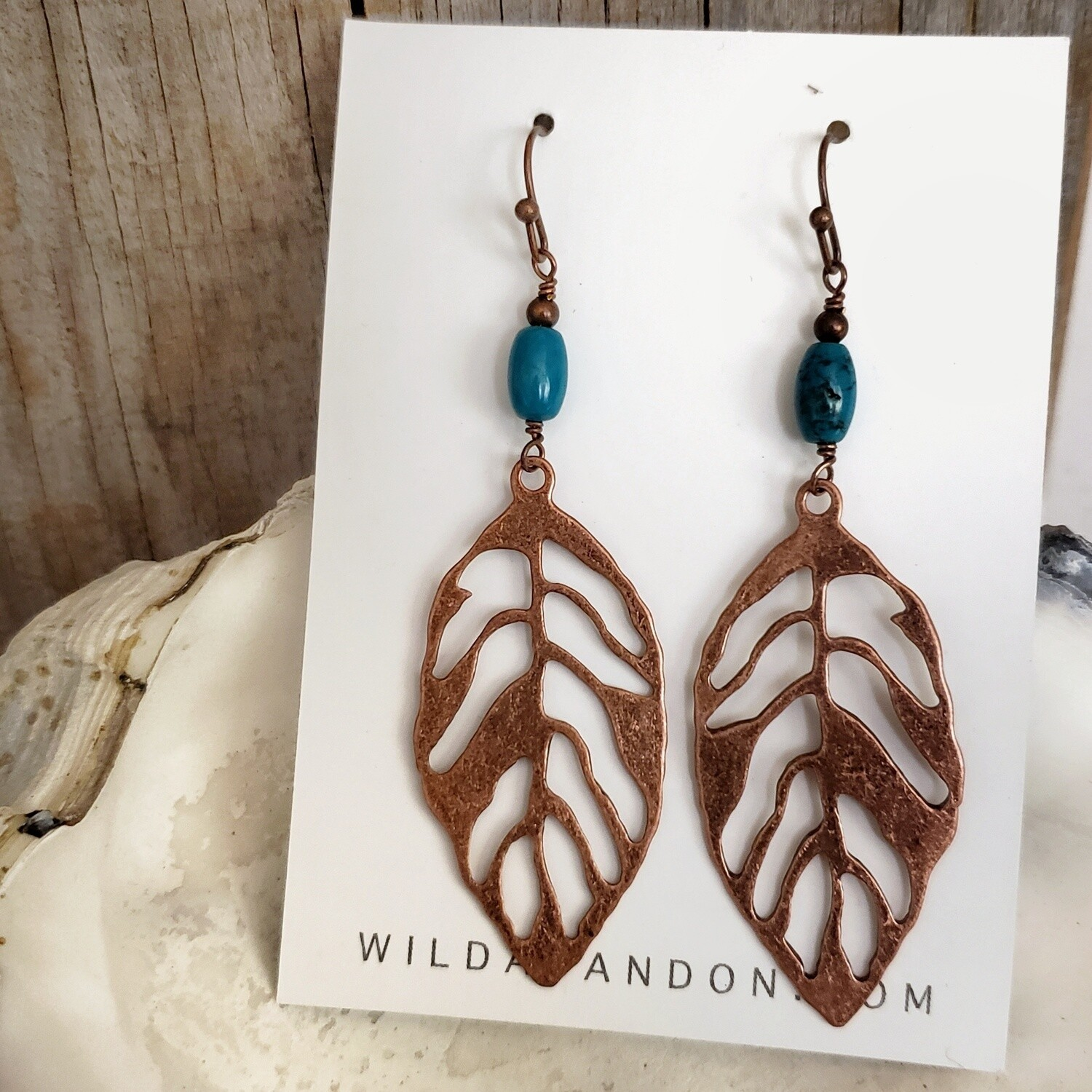 Wild Abandon Large Feather Earrings with cutout design and blue beads