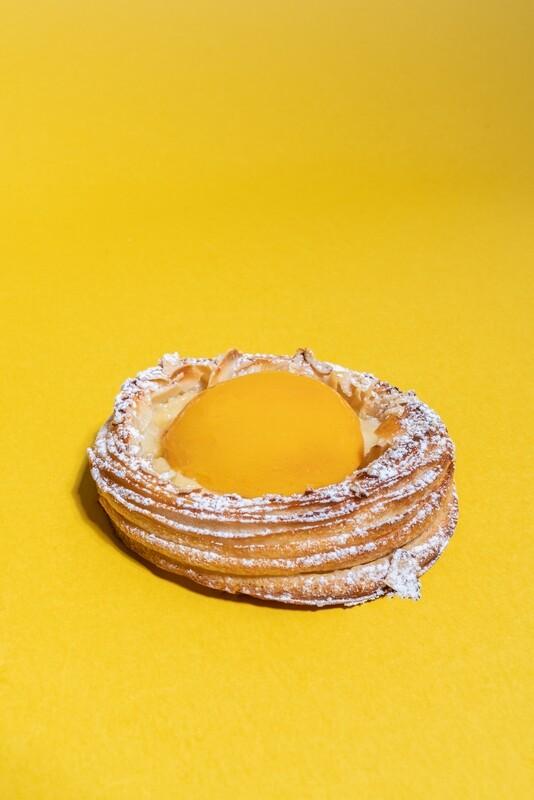 Sluoksniuotos tešlos pyragėlis su plikytu kremu, persiku ir migdolais