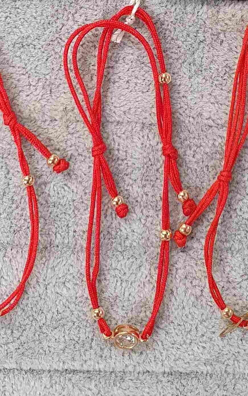 Raudono siūlo apyrankė su auksu apvaliu pakabuku ir akute